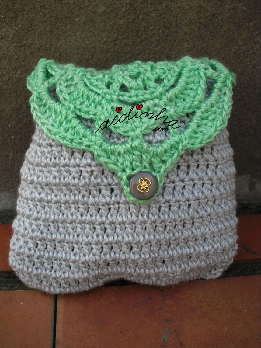 Bolsa cinza com roseta verde na tampa