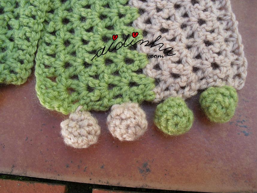 Pormenor dos berloques do cachecol infantil, verde e creme