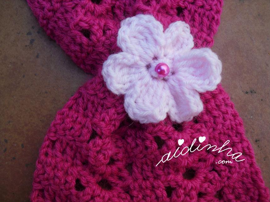 Pormenor da flor que franze as pontas do cachecol rosa choc