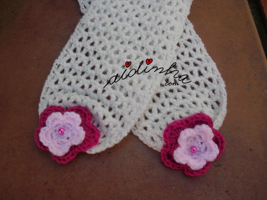 Vista das pontas do cachecol infantil, branco com flores rosa nas pontas