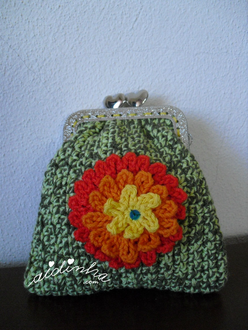 Foto mais pormenorizada da flor multicolorida da bolsa verde mesclada, de crochet