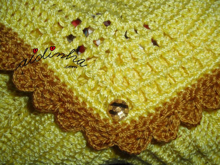 Vista pormenorizada do botão da bolsa, em crochet, tipo envelope, amarela