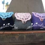 Bolsas, em crochet, nas cores azul, cinzenta e roxa, com roseta na tampa