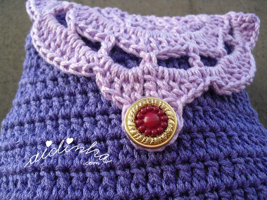 Vista de perto, da bolsa de crochet roxa com roseta lilás