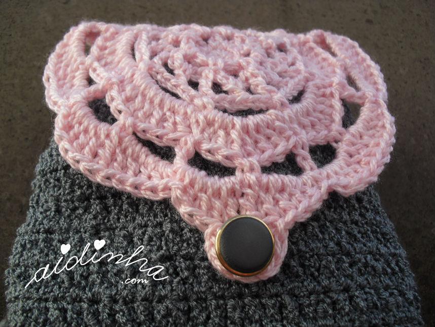 Vista de perto da bolsa de crochet, cinzenta com roseta rosa
