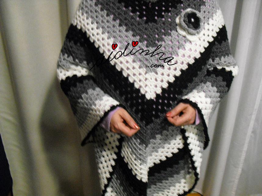 vista do poncho de crochet, com os braços levantados