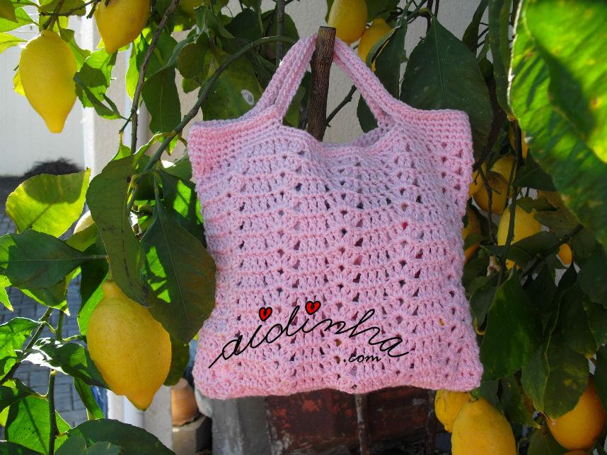 Bolsa de crochet rosa enquadrada no limoeiro