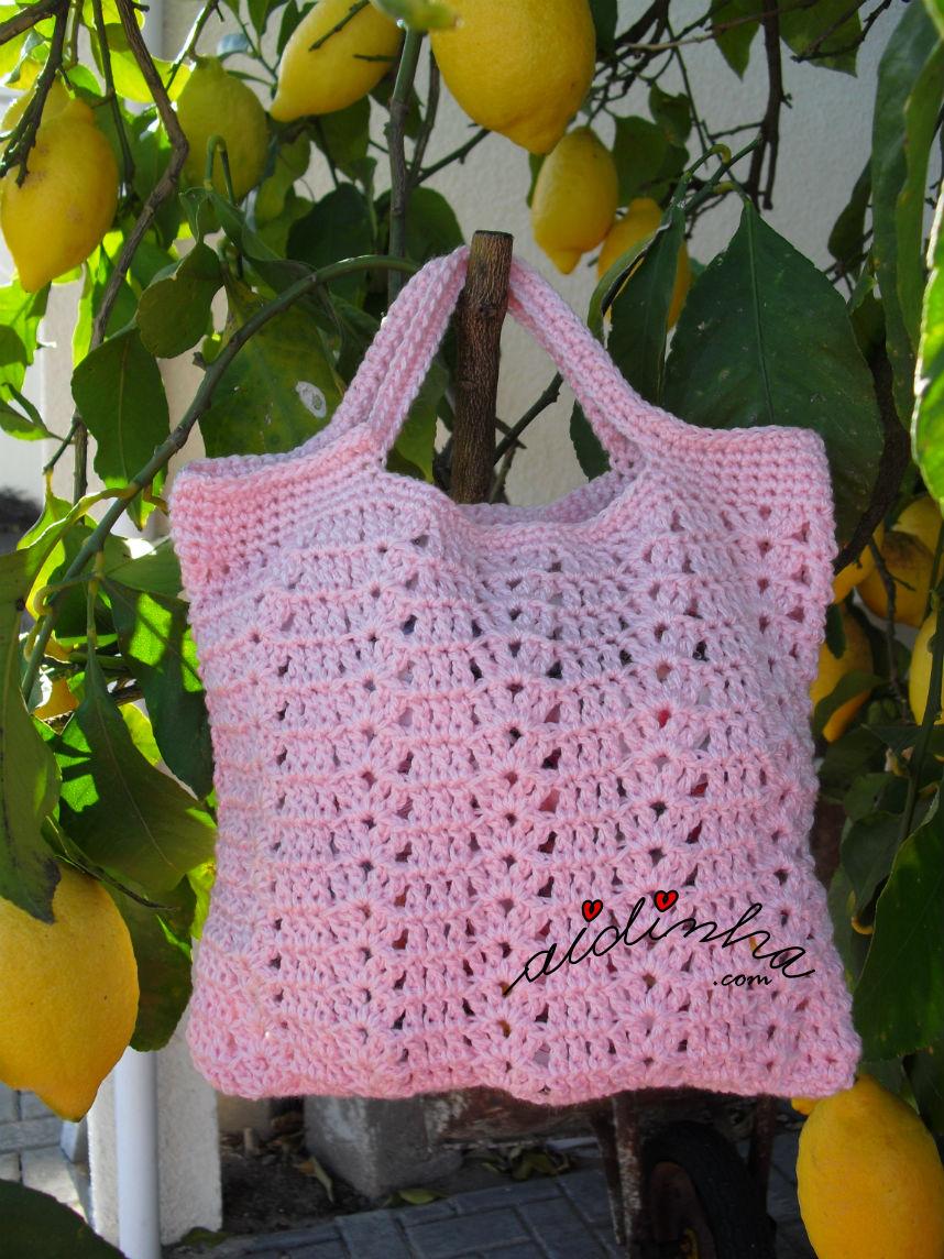 Vista total da bolsa, em crochet, rosa
