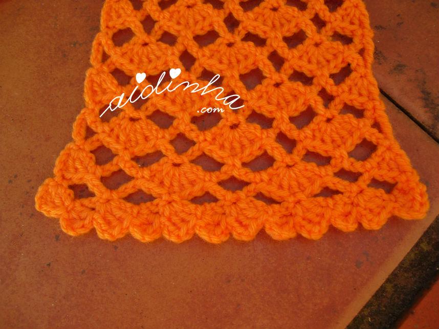 Vista de uma ponta do chachecol em crochet, laranja
