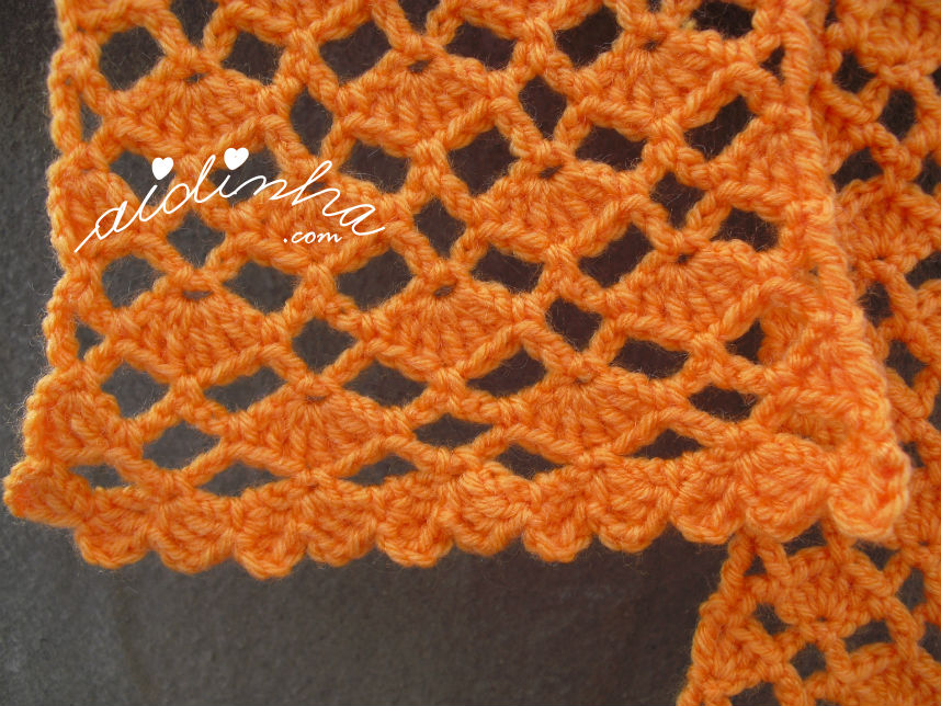 Vista mais aproximada, da ponta do cachecol em crochet, laranja