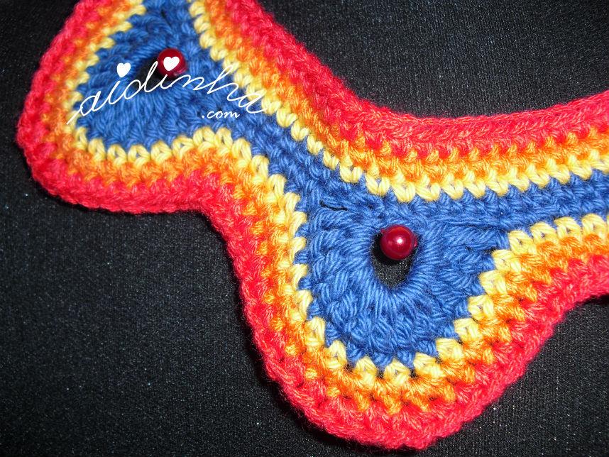 Foto pormenorizada de uma parte do colar, em crochet, multicolorido