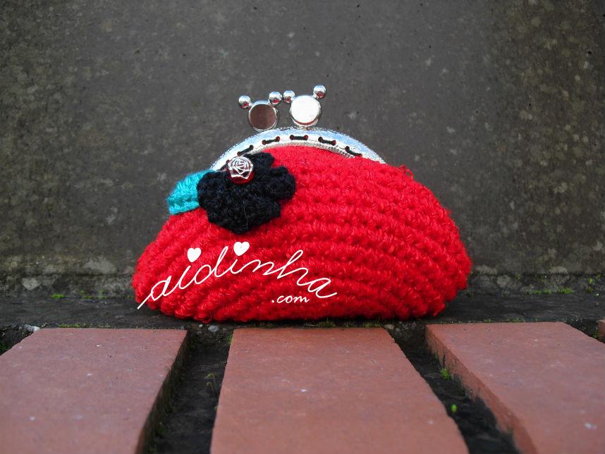 Outra vista da bolsa de crochet, redonda, vermelha com flor preta