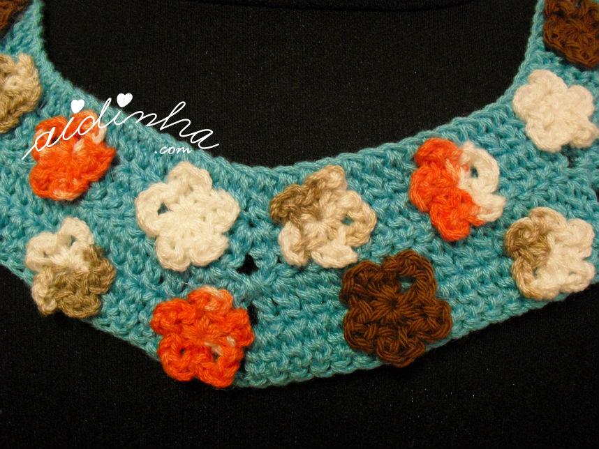 Pormenor das florinhas que compõem o colar de crochet, turquesa