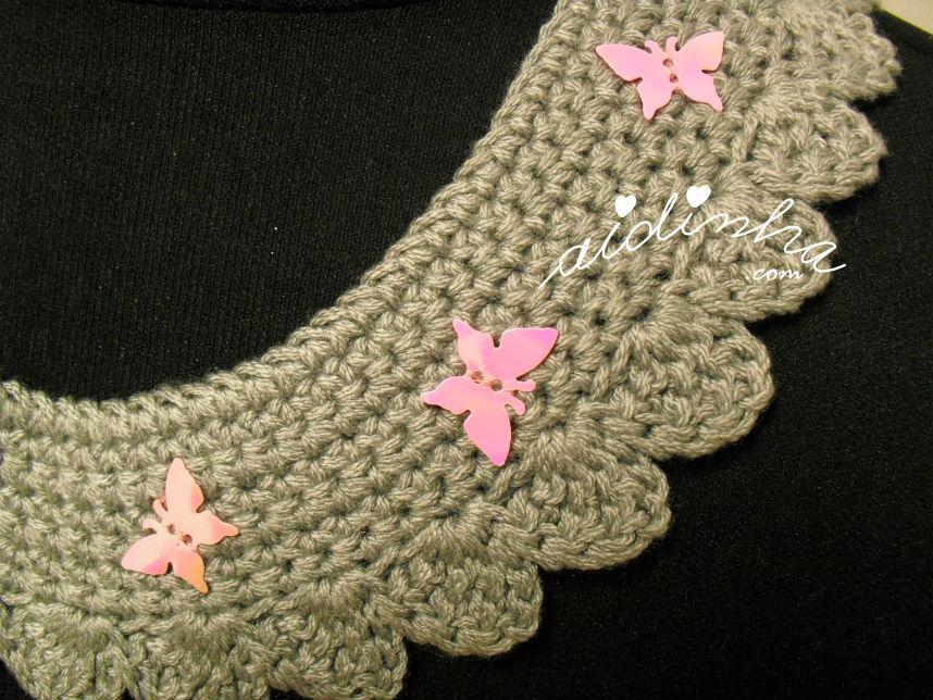 Vista de mais perto das borboletas rosa, do colar de crochet cinza