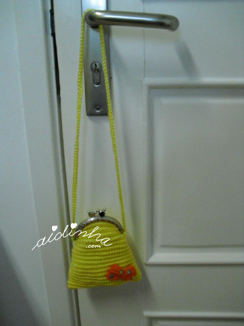 Vista geral da bolsa infantil, em crochet, amarela com lacinho
