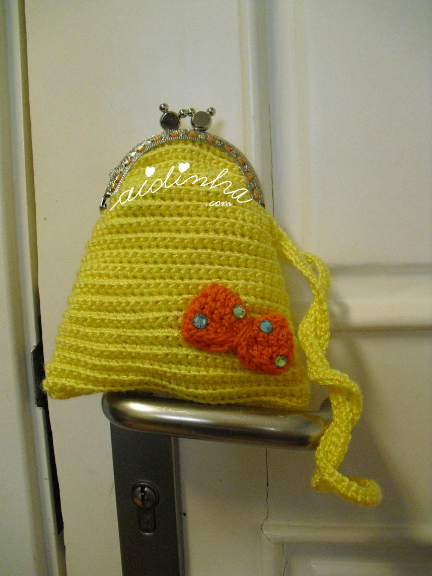Outra vista da bolsa infantil, em crochet, amarela com lacinho