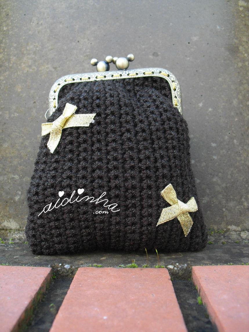 Outra foto da bolsa, em crochet, castanha com lacinhos dourados