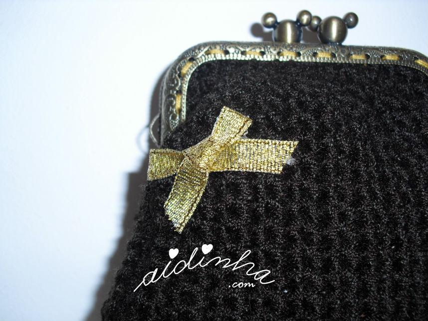 Pormenor do lacinho dourado, da bolsa de crochet castanha