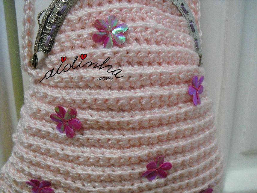 Pormenor das florinhas cosidas na bolsa infantil, de crochet