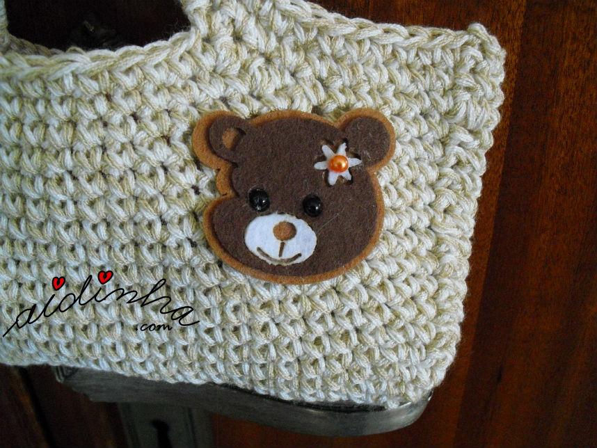 Pormenor do ursinho da bolsa infantil de crochet