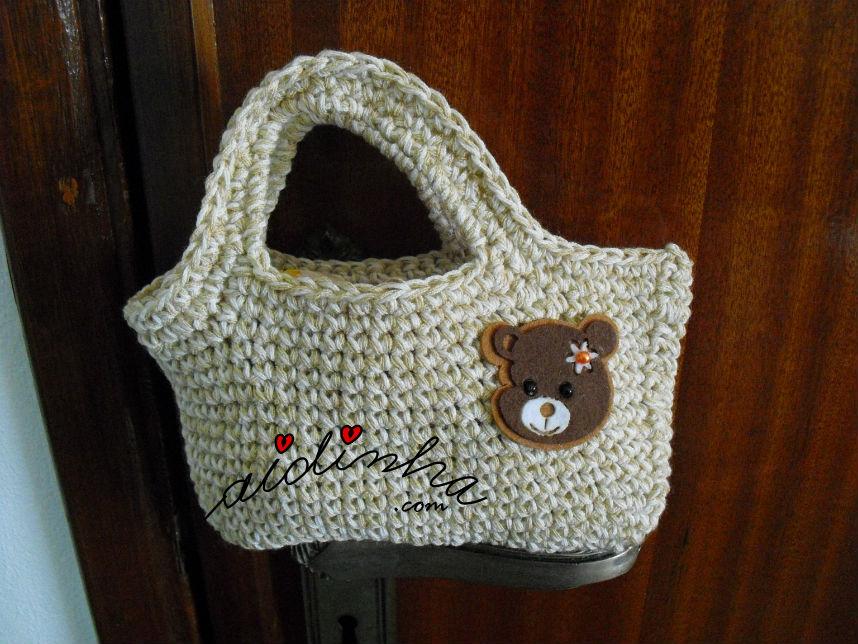 Outra foto da bolsa infantil, de crochet, creme com ursinho