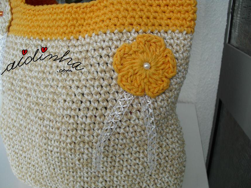 Pormenor da flor laranja, da bolsa de crochet com alças