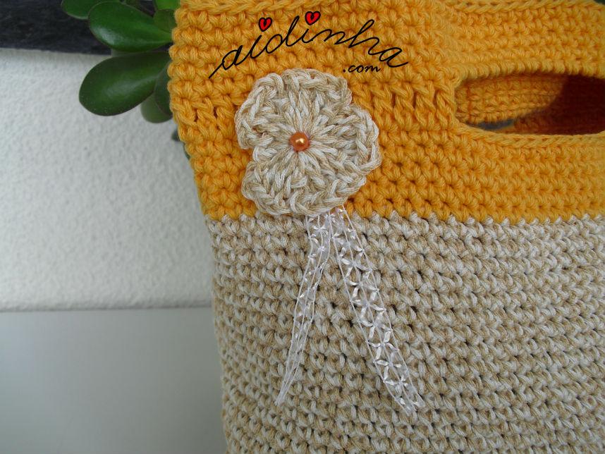 Pormenor da flor creme, da bolsa de crochet com alças