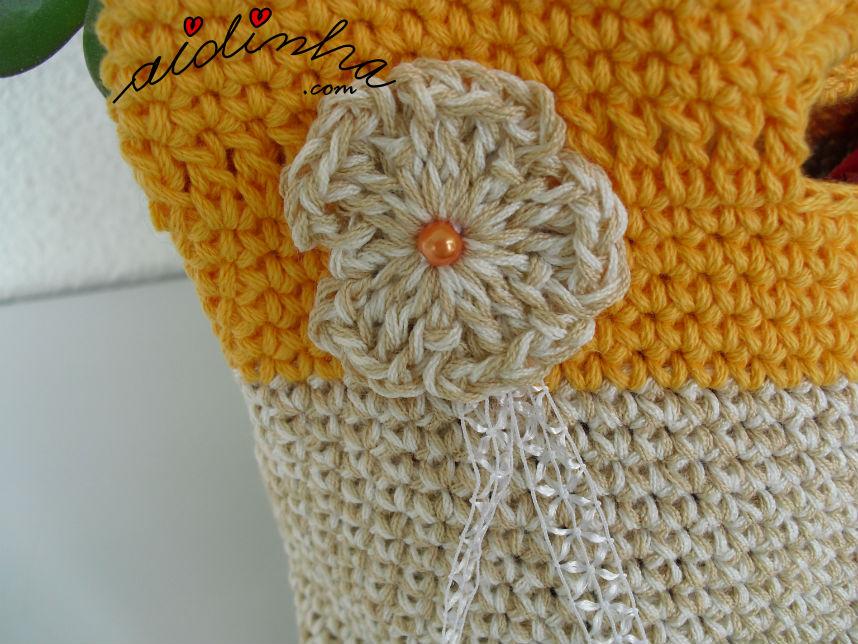 Vista de perto da flor creme, da bolsa de crochet, com alças