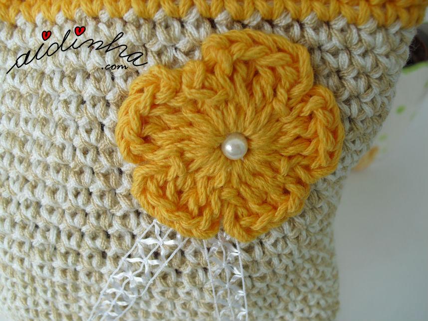 Vista de perto da flor laranja, da bolsa de crochet, com alças
