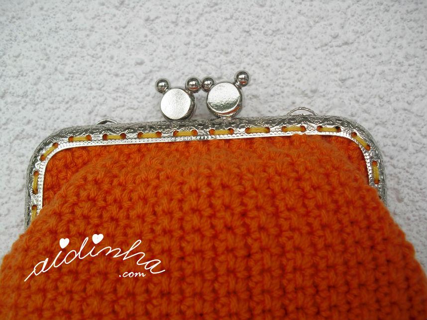 Pormenor do fecho cosido manualmente à bolsa, de crochet, laranja