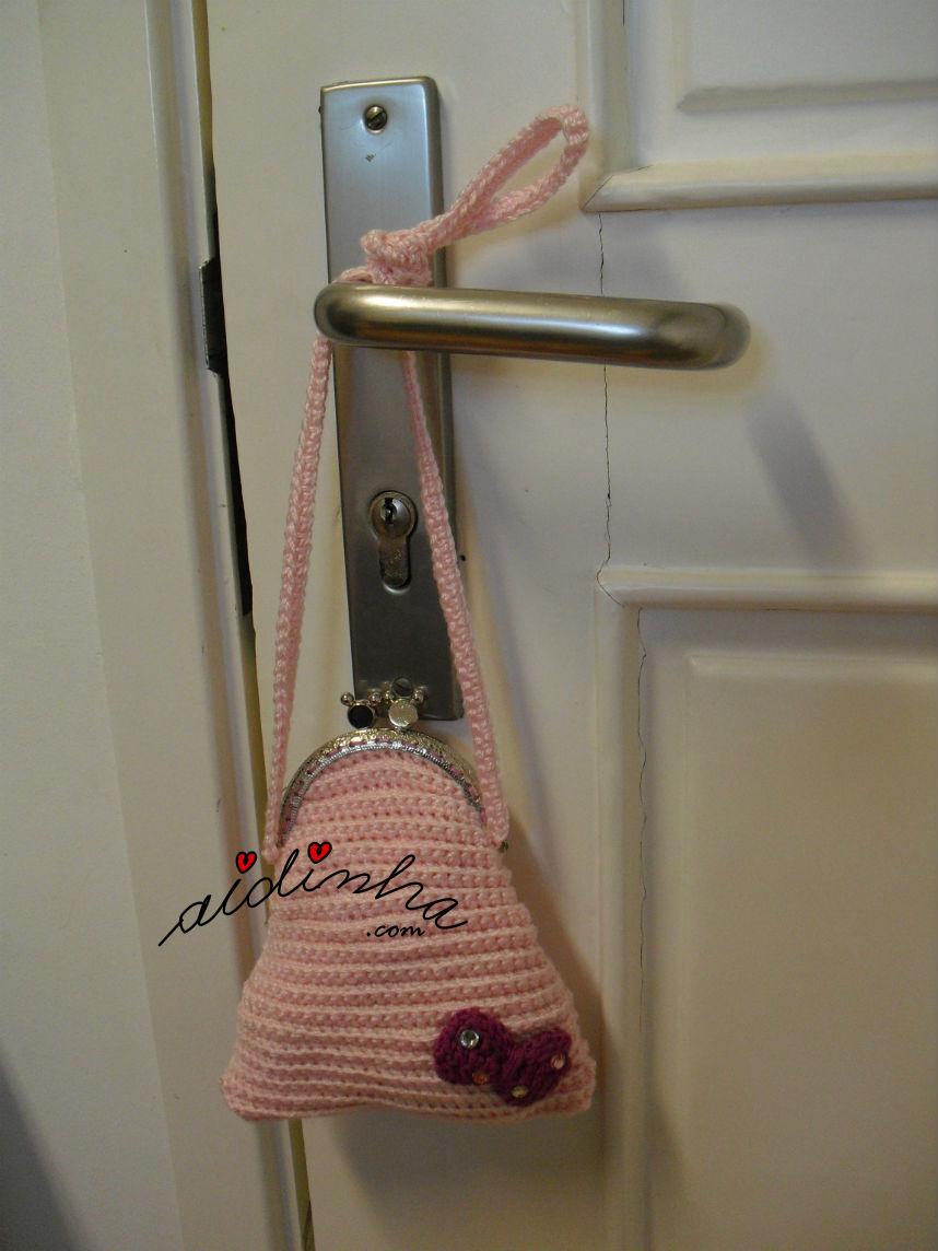Bolsa infantil, de crochet, rosa claro com lacinho, pendurada