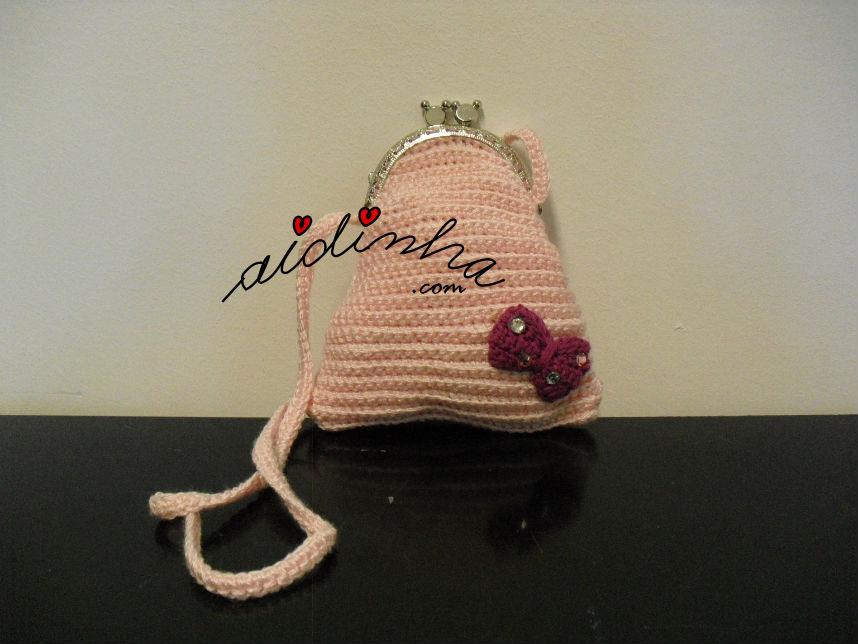 Vista total da bolsa infantil, de crochet, rosa claro com lacinho