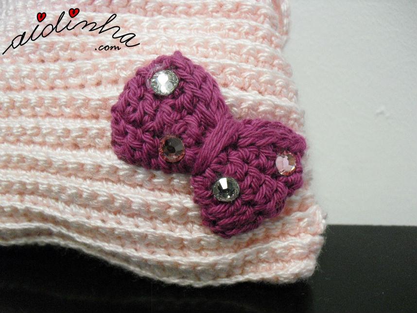 Vista, em pormenor, do lacinho da bolsa de crochet, rosa claro