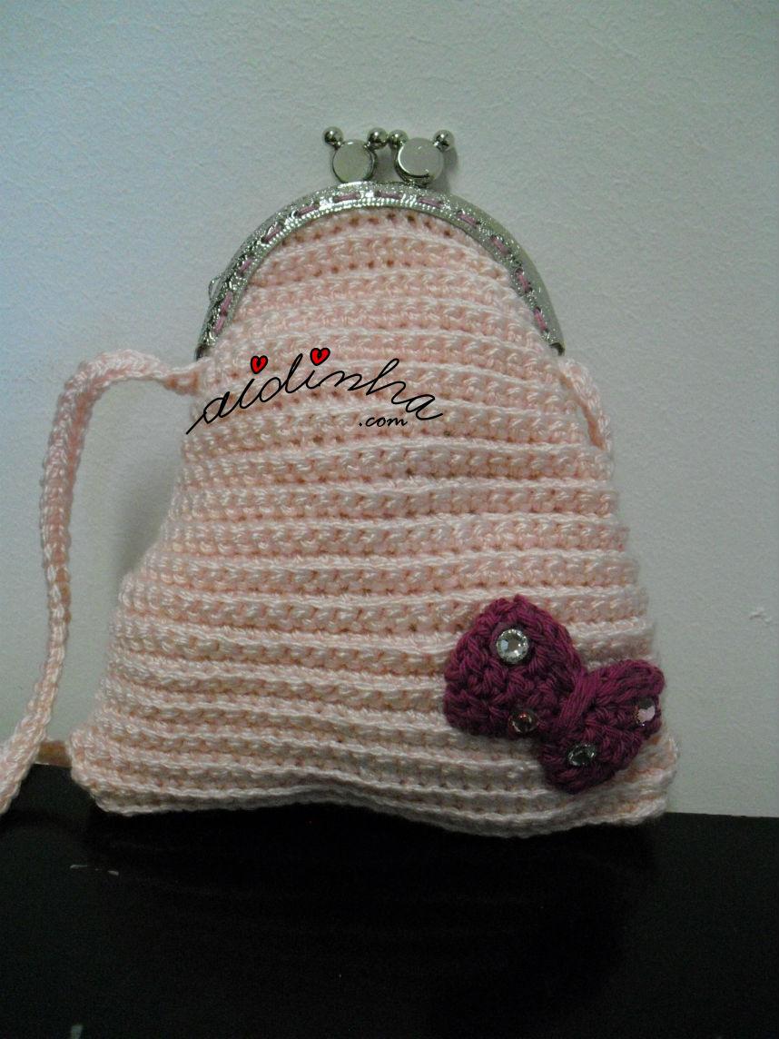 Vista mais próxima da bolsa infantil, em crochet, rosa claro com lacinho
