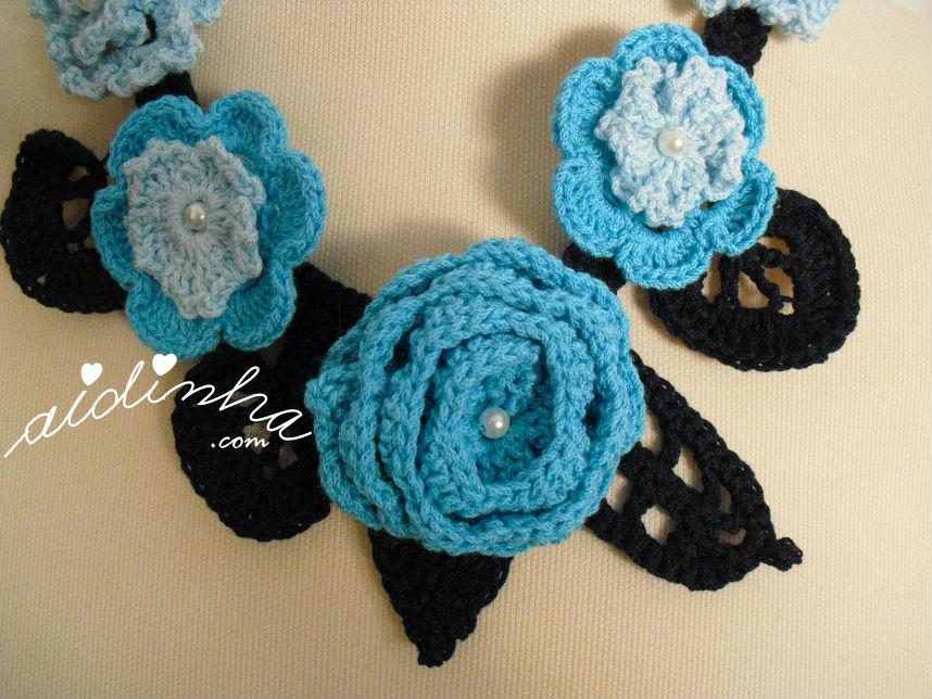 Vista de algumas flores, do colar de crochet, em tons de azul e turquesa