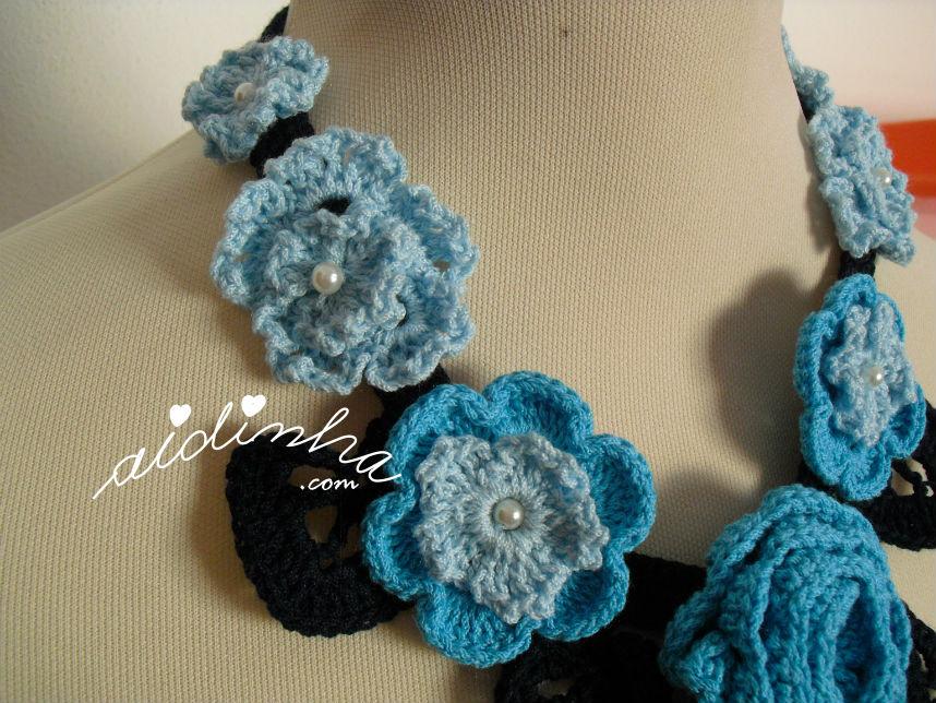 Vista das flores laterais, do colar de crochet, em tons de azul e turquesa