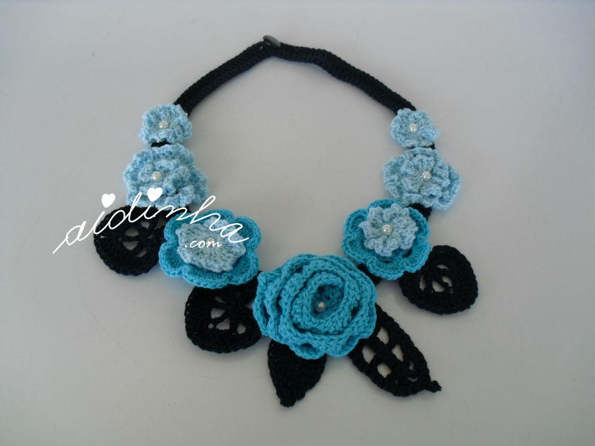Vista total do colar, em crochet, em tons de azul e turquesa