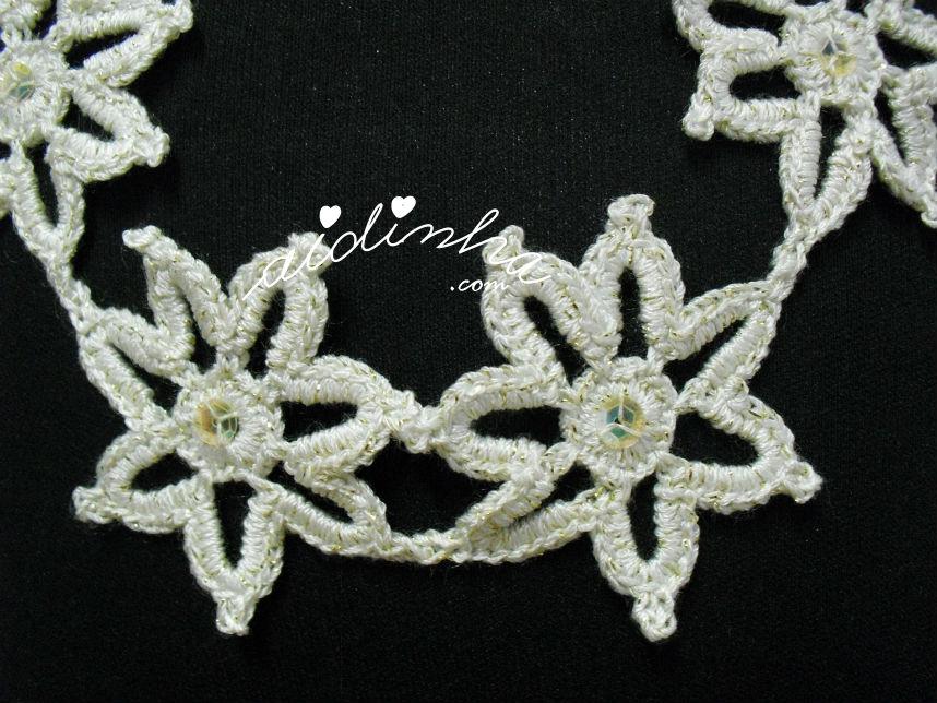 Vista, de perto, das flores do colar, de crochet, creme e dourado