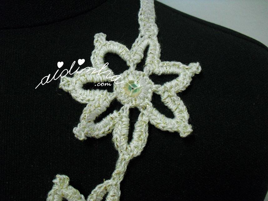 Flor que compõe o colar de crochet, creme e dourado