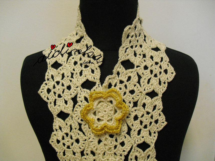 Vista, de frente, do cachecol, de crochet, com a flor
