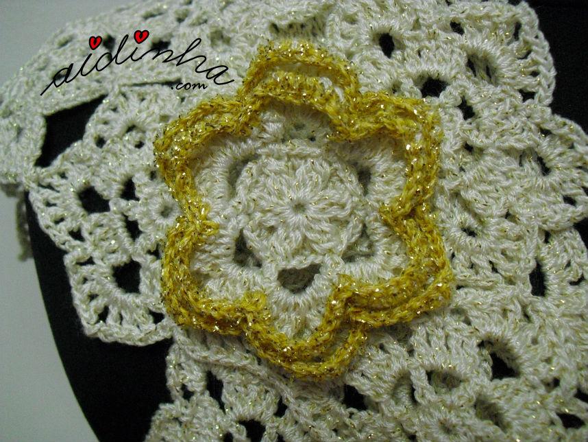 Vista, mais de perto, da flor do cachecol de crochet, creme e dourado