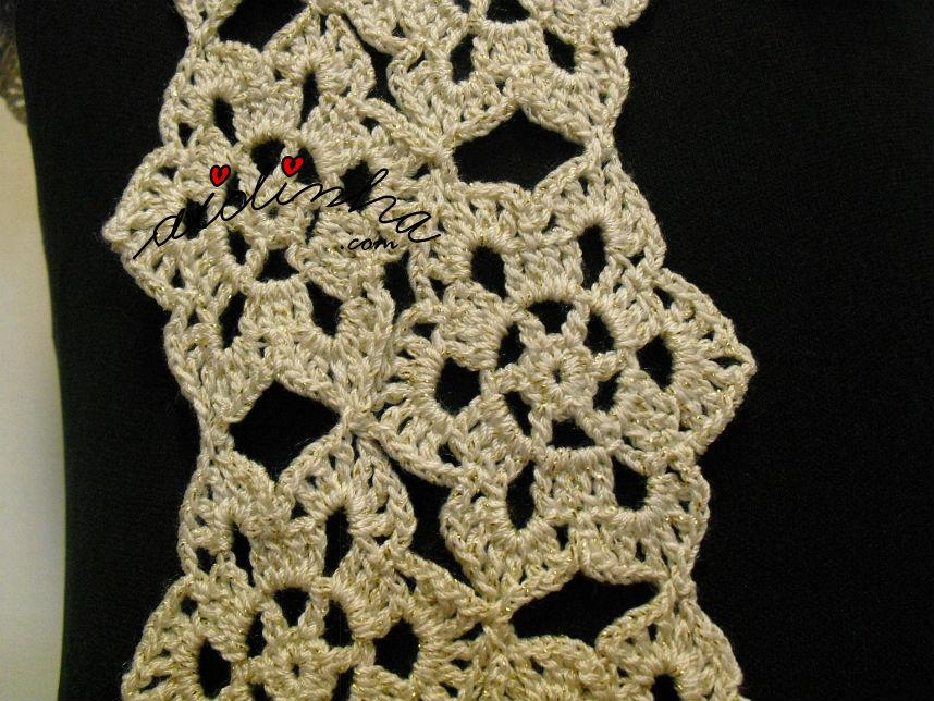 Pormenor da ligação das rosetas, do cachecol de crochet, creme e dourado