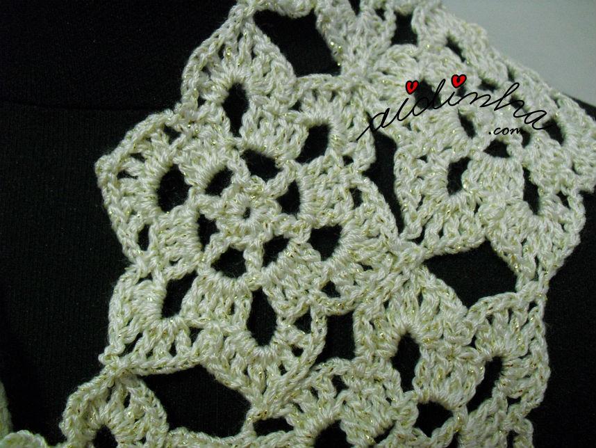 Pormenor de uma roseta do cachecol, de crochet, creme e dourado