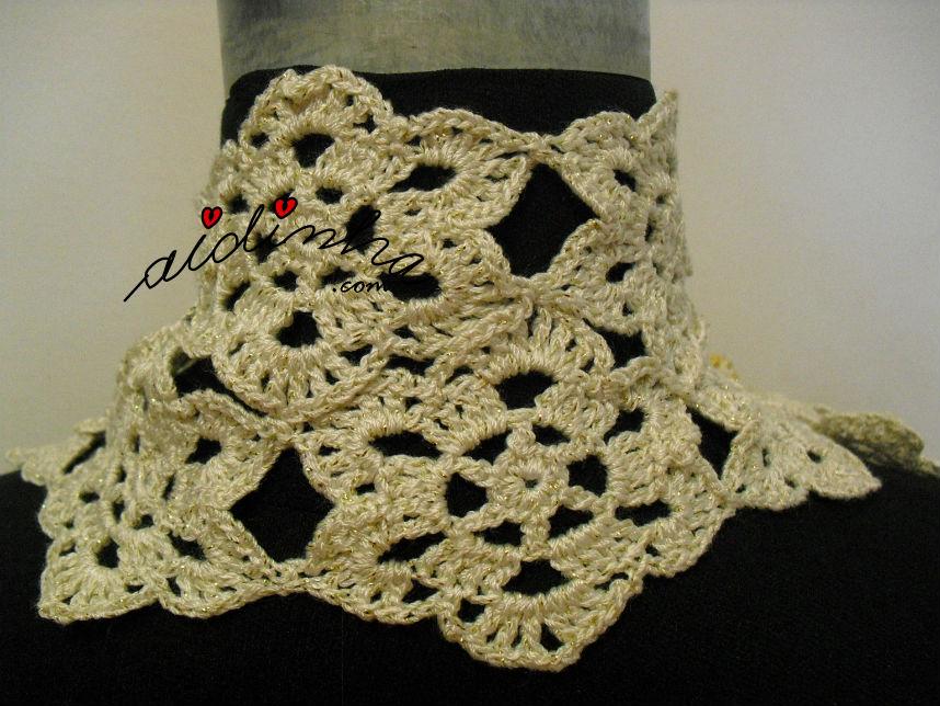 Vista da parte detrás do cachecol, de crochet, creme e dourado