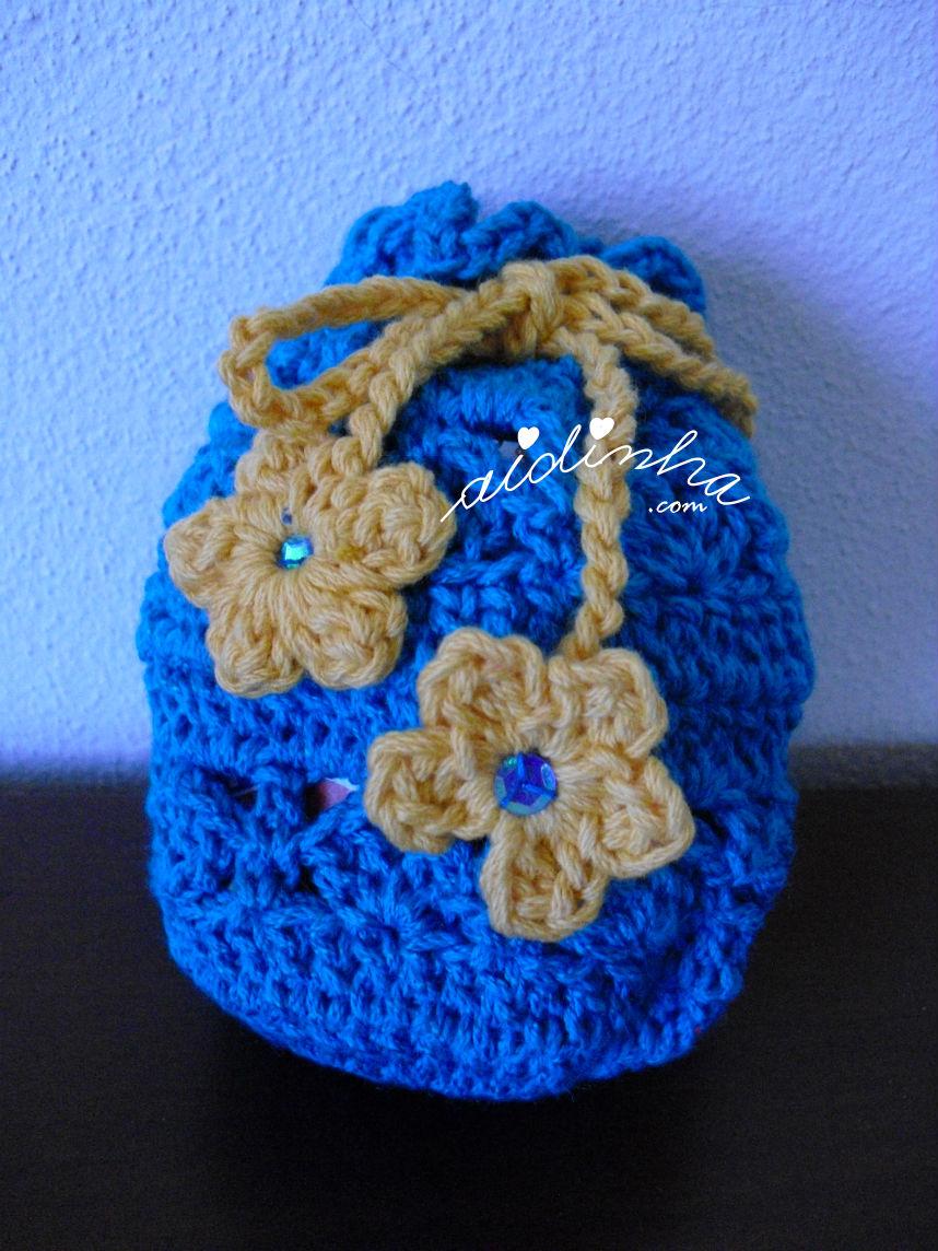 Outra foto da bolsa, em crochet, com feitio de saquinho, na cor turquesa