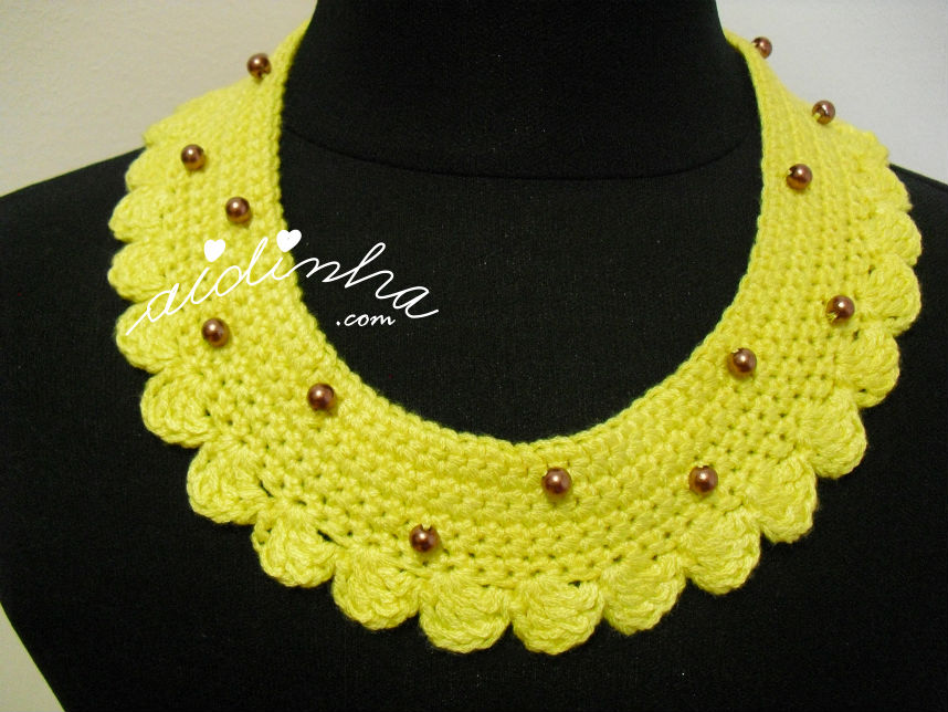 Vista total do colar de crochet amarelo, com pérolas