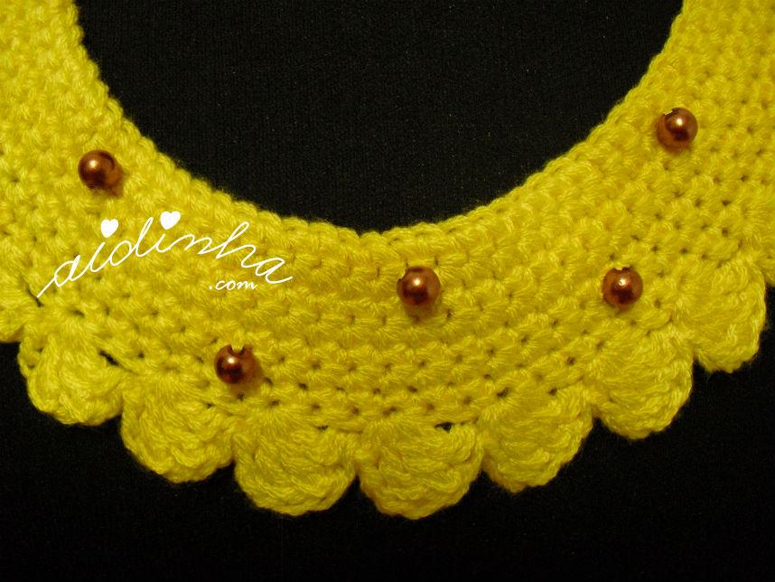 Vista de perto das pérolas aplicadas no colar de crochet amarelo