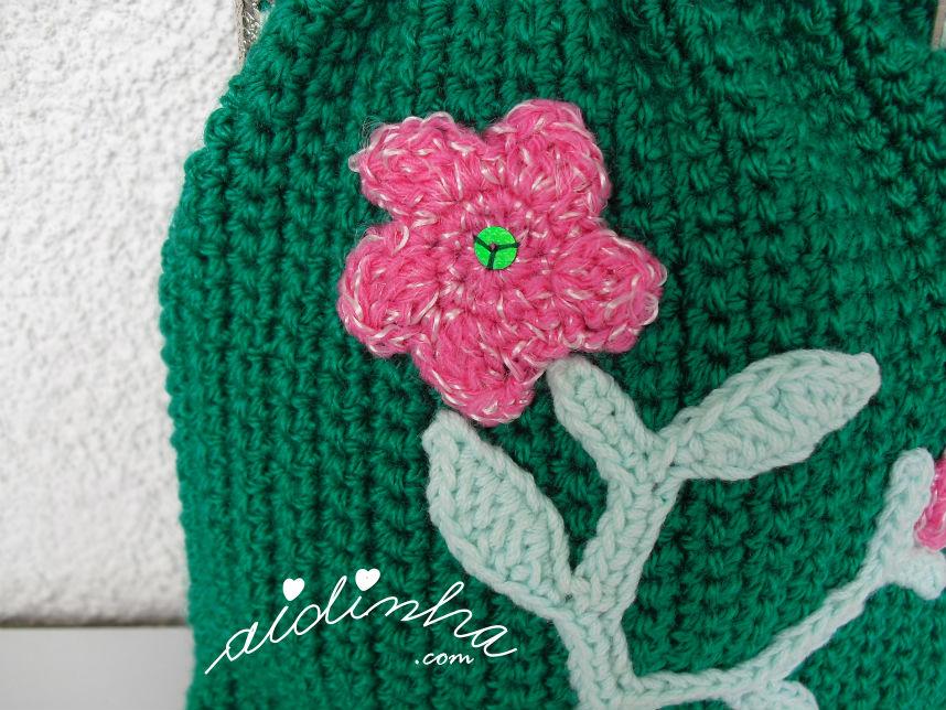 Pormenor da flor do ramo de crochet, da bolsa verde escura, de crochet