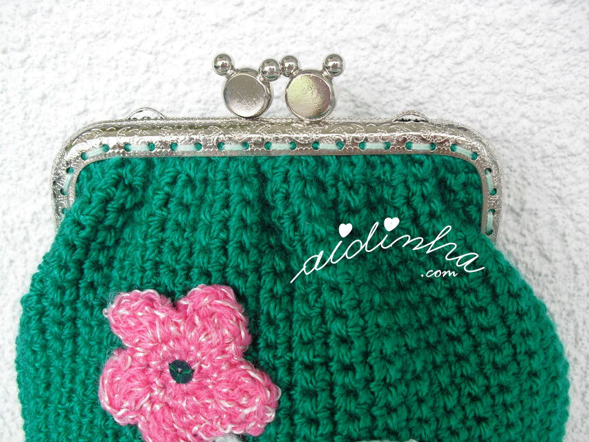 Pormenor do fecho cosido manualmente, da bolsa de crochet verde escura
