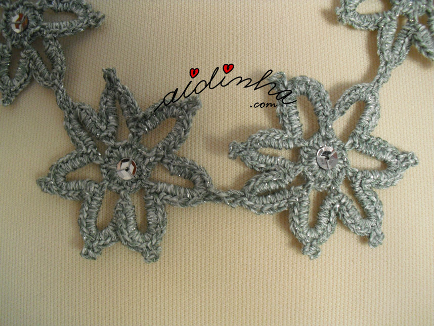 Vista de perto da união das flores que compõem o colar, de crochet, cinza e prata
